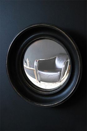 little aged black convex mirror angled on dark background lifestyle image