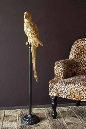 lifestyle image of Magnificent Tall Golden Parrot On His Perch with Rockett St George Leopard Love Armchair and dark purple wall background