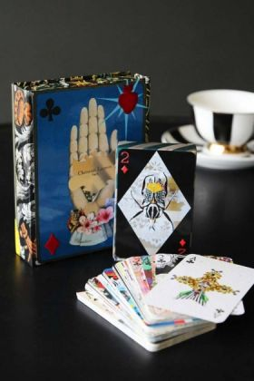lifestyle image of maison de jeu by christian lacroix playing cards out of box on black table with black and white striped teacup and saucer