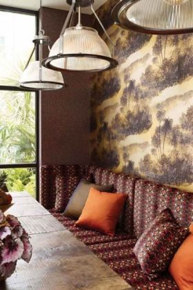 lifestyle image of matthew williamson cocos wallpaper behind burgandy sofa and orange cushions with three ceiling lights and wooden table