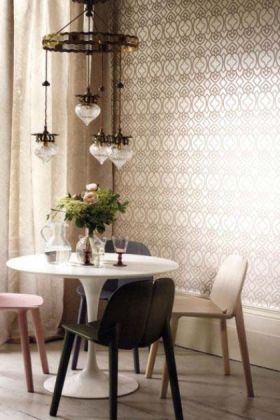lifestyle image of Matthew Williamson Imperial Lattice Wallpaper with white round dining table and coloured dining chairs with plant and ceiling light above