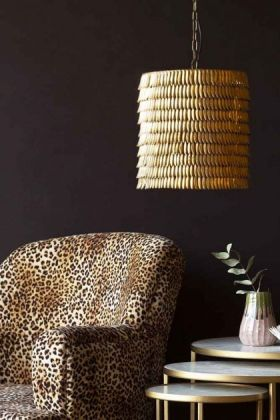 Lifestyle image of the Metallic Feather Effect Pendant Light with leopard love armchair and nest of marble tables on dark wall background
