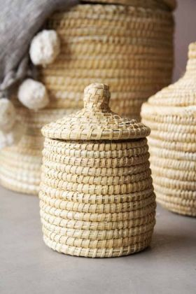 lifestyle image of the Extra Small Moroccan Wicket Basket with lid on the top and other baskets in background as well as a grey pom pom blanket