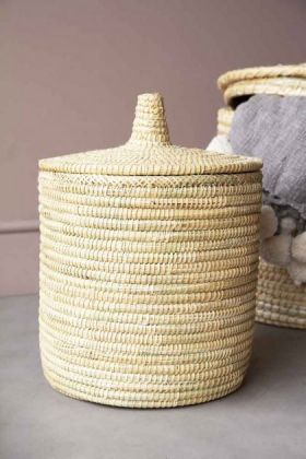 lifestyle image of Medium-sized Moroccan Wicket Basket with lid on the top and other baskets and grey blanket in background with grey flooring and pale wall background
