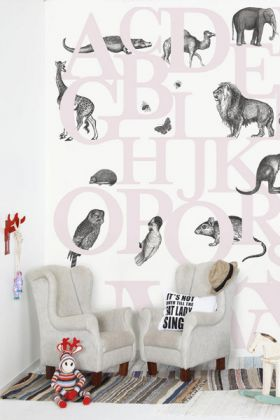 lifestyle image of mr perswall wallpaper - hide & seek collection - abc you - pink with two pale armchairs on striped rug and with childrens toys