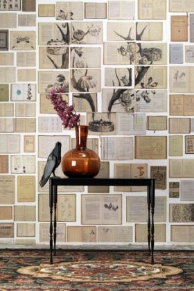 lifestyle image of nlxl eks02 biblioteca wallpaper by ekaterina panikanova - mural 2: antlers with black table and brown vase with pink flower in
