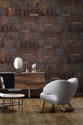 Lifestyle image of NLXL PHE-19 Rusted Metal Wallpaper by Piet Hein Eek with grey arm chair and side board with white table lamp on top and wooden flooring