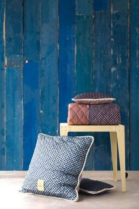 lifestyle image of NLXL PHM-36 Blue Scrapwood Wallpaper By Piet Hein Eek with wooden side table and blue cushion