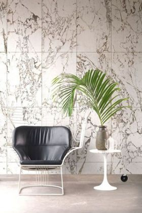 lifestyle image of nlxl phm-41a white marble wallpaper by piet hein eek with black and white chair and white side table with plant on