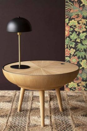 Lifestyle image of the Oak Curve Coffee Table With Removable Lid with table lamp on top and Rockett St George Oriental Garden Wallpaper in background on woven flooring