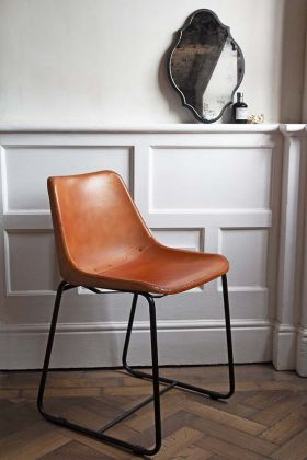 Lifestyle image of the Industrial Leather Dining Chair - Brown with Black Legs with black mirror and wooden parquet floor with white detailed wall background