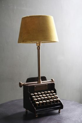 lifestyle image of qwerty typewriter table lamp with yellow lamp shade on black table and grey wall background