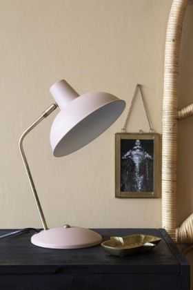 Lifestyle image of the Retro Desk Lamp - Pale Pink on black surface with picture frame on pale wall background
