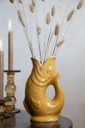 Lifestyle image of the Amber Ceramic Fish Jug with faux stems