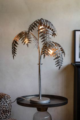 Lifestyle image of the Antique Silver Palm Leaf Table Lamp switched on