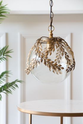 Lifestyle image of the Ornate Globe Pendant Ceiling Light With Brass Leaf Detailing with a table below