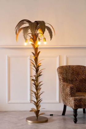 Lifestyle image of the Beautiful Vintage-Style Palm Tree Floor Lamp lit up on a light background