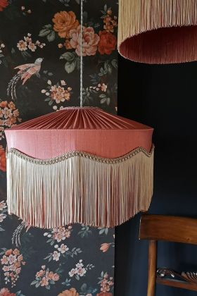 Lifestyle image of the Bespoke Coral Hibiscus Silk Tiffany Lamp Shade with wavy and straight fringe in front of floral background
