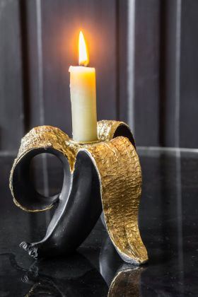 Image of the Black And Gold Banana Candle Holder with a lit candle