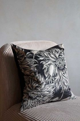 Image of the Monochrome Poppy Flower Velvet Cushion sat on a chair