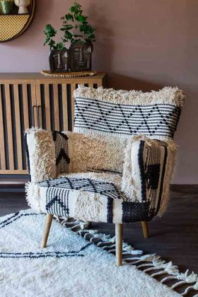 lifestyle image of shaggy Boho Woven Armchair on pink background with wooden sideboard and soft white berber rug with tassels