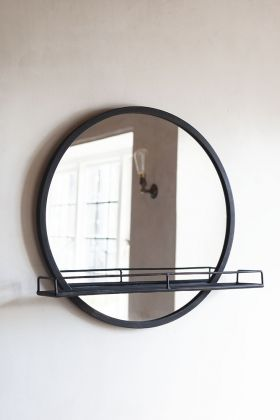 Lifestyle image of the Black Metal Round Mirror With Shelf hanging on the wall