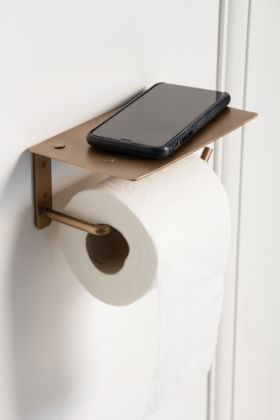 Lifestyle image of the Brass Effect Toilet Roll Holder with a mobile phone on the ledge