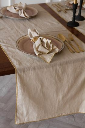 Lifestyle image of the Champagne Cotton Table Runner With Gold Trim