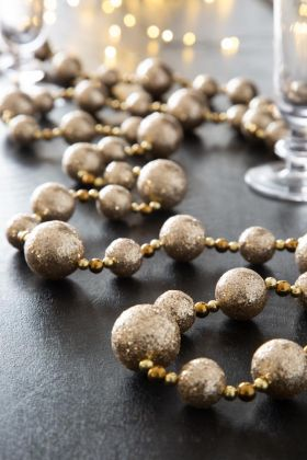Lifestyle image of the Champagne Glitter Ball Garland on a Christmas dinner table