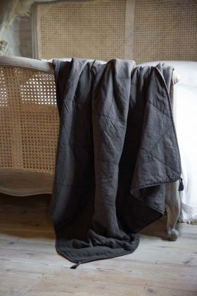 Image of the Charcoal Grey Cotton Throw With Tassels draped over the end of a bed