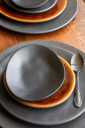 Image of the Christian Tortu Riviera Matt Black Side Plate on top of a mustard plate