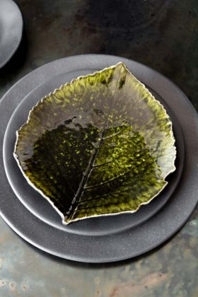 Image of the Christian Tortu Riviera Olive Green Leaf Plate on top of black plates