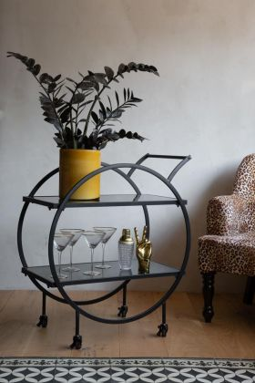 Lifestyle image of the Contemporary Round Black & Smoked Glass Drinks Trolley