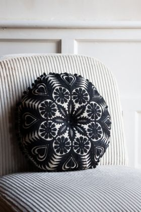 Lifestyle image of the Cool Cotton Crochet Cushion With Pom Pom Edging sat on a chair