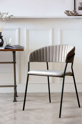 Lifestyle image of Curved Back Velvet Dining Chair In Mink Grey with panelled wall