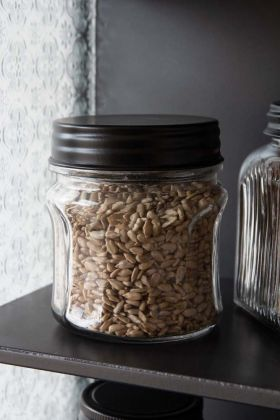 Lifestyle image of the Curvy Glass Storage Jar With Black Metal Lid