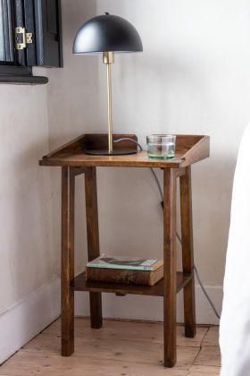 Lifestyle image of the Dark Mango Wood Bedside Table With Cable Gap with books on the bottom shelf