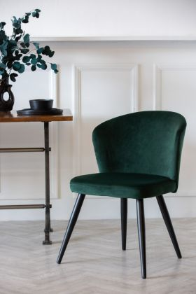 Lifestyle image of Rich Green Deco Velvet Dining Chair on white panelled wall