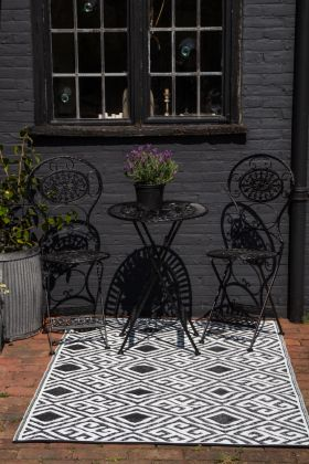 Lifestyle image of the dark side of the Diamond Key Pattern Reversible Outdoor Garden Rug