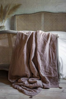 Image of the Dusty Pink Cotton Throw With Tassels draped on the end of a bed