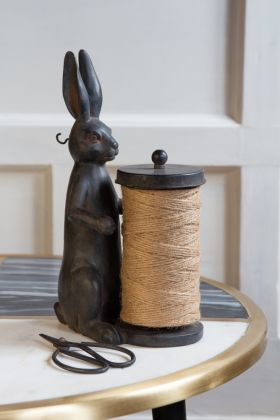 Lifestyle image of the Distressed Antique Rabbit String Container & Scissors