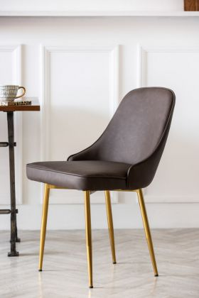 Lifestyle image of Faux Leather Dining Chair With Brass Legs - Brown on white panelled wall background and coffee cup on dining table