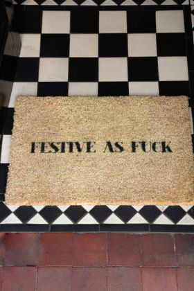 Image of the Festive As Fuck Christmas Doormat on a tiled floor