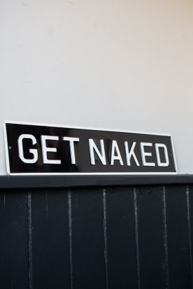 Angled image of the Get Naked Metal Sign Wall Art