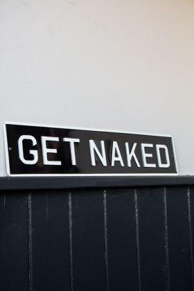 Angled image of the Get Naked Metal Sign Wall Art