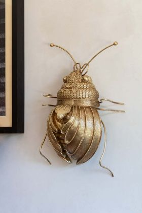 Lifestyle image of the Gold Beetle Wall Hanging on the wall