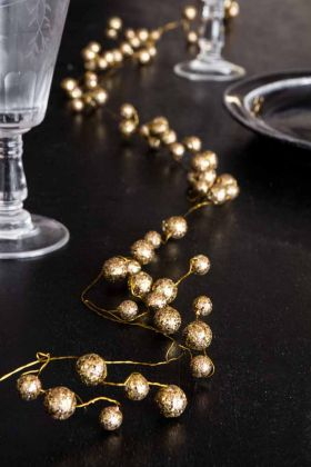 Image of the Gold Glitter Ball Garland Spray Decoration on a Christmas dinner table