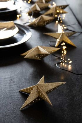 Lifestyle image of the Light Gold Glitter Star Christmas Tree Decoration scattered on a Christmas dining table