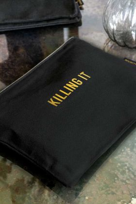 Lifestyle image of the Black Cotton Killing It Pouch Wash Bag