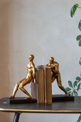 Lifestyle image of the Antique Gold Strong Man Bookends